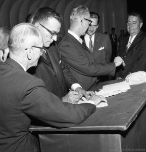Cinq hommes signent un bail.