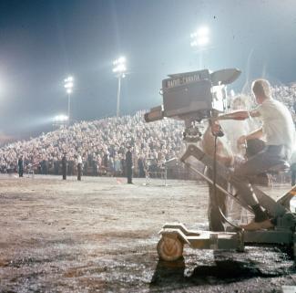 Télédiffusion pancanadienne de la cérémonie. On voit une caméra et la foule assise dans les gradins.