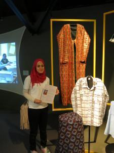 Une élève pose avec son trésor de famille dans l'exposition «J'arrive à Montréal».