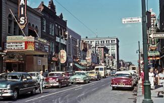 Photo couleur de la rue Sainte-Catherine à partir de la rue Saint-Dominique dans les années 1950 avec des voitures et les édifices commerciaux de chaque côté et leurs enseignes.