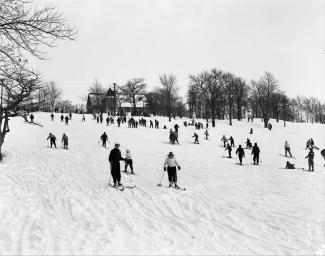 Photographie en contre-plongée de gens descendant une piste enneigée en ski.