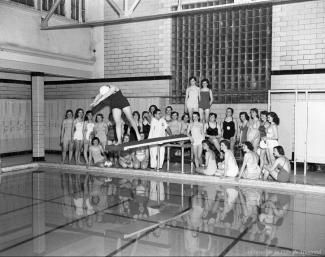 Reportage photographique sur un groupe de jeunes filles du High School au bain Lévesque. On y voit les jeunes filles dans la piscine et au plongeoir sur la présente photo.