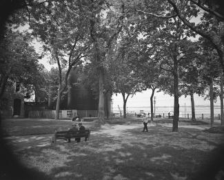 Photo en noir et blanc d'un parc avec de grands arbres sur le bord de l'eau. Deux hommes sont assis sur un banc et un autre homme marche. Des réservoirs à mélasse sont situés à l'arrière-planà gauche de la photo.