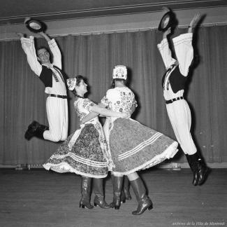 Deux danseurs sautent et sont de chaque côté de deux danseuses qui se tiennent par la taille. Ils sont tous en costume folklorique hongrois.