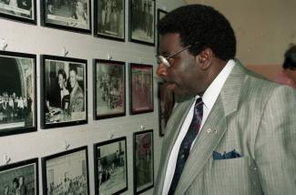 Le pianiste jazz Oliver Jones regardant un mur de photos encadrées au Negro Community Centre