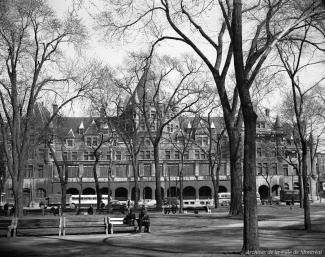 Photographie du square Viger et de l'édifice Jacques-Viger à travers les arbres.