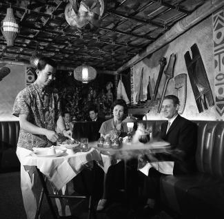 Photographie en noir et blanc de deux couples attablés. Le couple à l'avant est servi par un cuisinier et de la fumée s'échappe des verres sur la table.