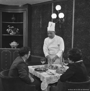 Photographie en noir et blanc représentant un couple à table, de dos, devant lequel se tient un chef chinois qui s'apprête à leur servir un plat.