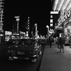 Scène de rue en soirée, avec les néons, des gens qui se promènent et des voitures