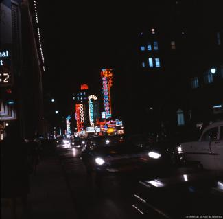 Photo couleur de la rue Sainte-Catherine la nuit avec des enseignes au néon et des voitures au premier plan.