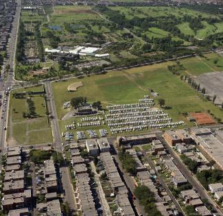 Vue aérienne couleur montrant un parc, des édifices et des rues.