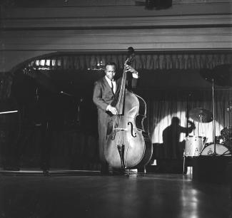 Photographie en noir et blanc d'un homme noir jouant de la contrebasse sur une scène.