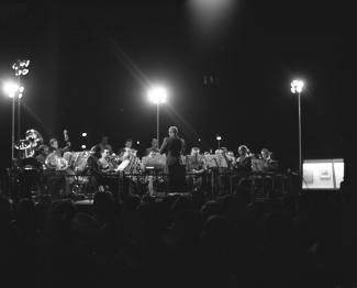 Photo noir et blanc d'un ensemble d'harmonie jouant dans un square le soir.
