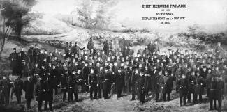 Photographie en noir et blanc d'un groupe de policiers en uniforme. Il y a une inscription dans le coin supérieur droit.