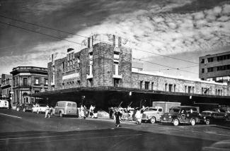 Photo en noir et blanc montrant un édifice abritant un marché vu du coin de la rue. Des voitures et des gens circulent.