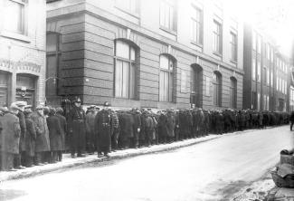 Photographie d'une file d'attente de chômeurs devant l'entrée du refuge Meurling (435, rue du Champ-de-Mars) lors de la crise économique des années 1930.