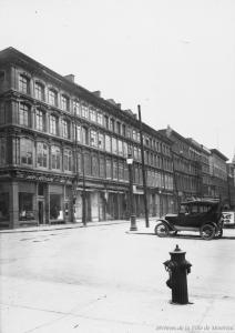 Photographie d'une enfilade de bâtiments à fenêtres le long de la rue Notre-Dame, et d'un angle de rue, vus de l'ouest.