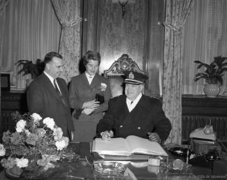 Signature du livre d'or à l'hôtel de ville de Montréal. Le maire Sarto Fournier et une femme sont debout, alors que le chef de police est assis, crayon en main pour signer.