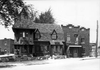 Photo en noir et blanc montrant le restaurant Au lutin et un duplex adjacent au restaurant.