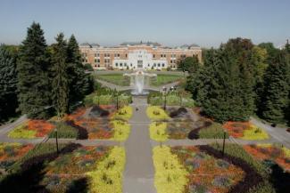 Photographie couleur de la façade de l'édifice Marie-Victorin et des jardins d'accueil à l'avant.