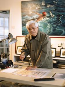 Photo couleur d'un artiste tenant un pinceau dans une main et l'autre main appuyée sur une table dans son atelier.