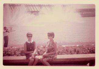 Yolande et sa sœur prennent la pose assises sur le bord d'une fontaine