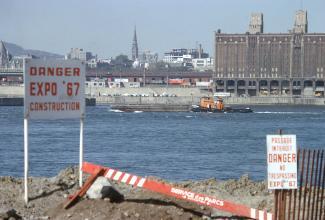 """Vue montrant à l'avant-plan l'île Sainte-Hélène  avec un panneau disant \""""Danger Expo 67 Construction\"""", avec Montréal à l'arrière-plan."""