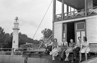 Six hommes et femmes sont assis sur la galerie devant un pavillon en bas. Un phare se trouve à gauche de la photo en noir et blanc.