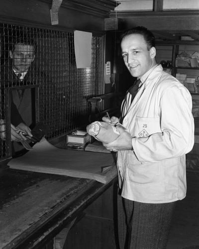 Photographie en noir et blanc d'un homme portant un sarrau avec le logo de la Commission des liqueurs et tenant une bouteille. Derrière la grille se tient un client.