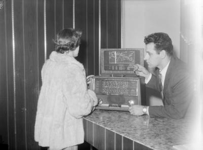 Une cliente, conseillée par un vendeur, vérifie un poste de radio « Hallicrafters World-Wide » au comptoir du magasin Modern Radio Service Inc. Une carte du monde divisée en 24 fuseaux horaires est placée au-dessus de l'appareil