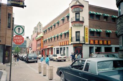 Photo couleur montrant l'intersection des rues Clark et De la Gauchetière dans le Quartier chinois. Le café Nanking est au coin de la rue.