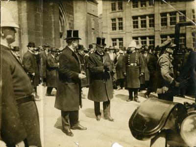 Photo d'un groupe d'hommes portant chapeau et costume sur le parvis d'un édifice (église?), des policiers sont présents.