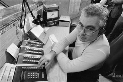 Photo en noir et blanc d'un homme portant un casque d'écoute et assis devant un bureau avec des appareils pour le service d'urgence 911.