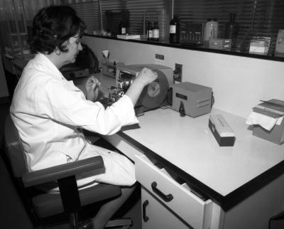 Une femme portant un sarrau est assise à un bureau dans un laboratoire et manipule un appareil.