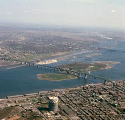 Vue aérienne en couleur montrant au centre le fleuve Saint-Laurent et le pont Jacques-Cartier, avec une partie des rives de Montréal et de la Rive-Sud.