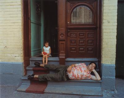 Un homme fait la sieste sur le pas de la porte sous le regard d'une petite fille.