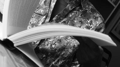 Photo en noir et blanc montrant en plan rapproché une personne qui tourne les pages d'un cahier relié.