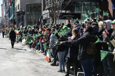 Une foule brandit des drapeaux verts rue Sainte-Catherine en attente du défilé.