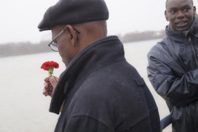 Un Rwandais tient une fleur rouge dans sa main et un autre homme si tient à côté