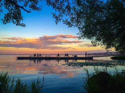 Scène au bord de l'eau avec un ciel de soirée aux couleurs chaudes et neuf personnes assises sur un quai.