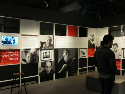 Salle d'exposition montrant deux murs avec des photos en noir et blanc, des panneaux de texte, un écran et deux personnes, debout, qui la visitent.
