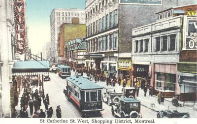 Carte postale de la rue Sainte-Catherine avec un tramway et des voitures qui circulent dans la rue.