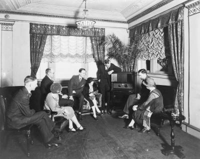 Groupe de personnes réunies autour d'un récepteur radio dans les années 1920.