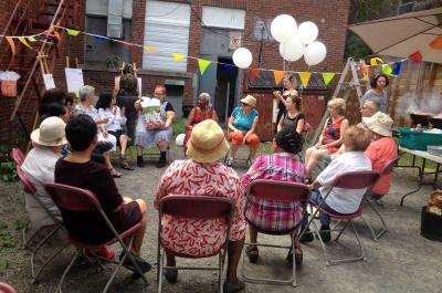 Dix-sept personnes sont assises en cercle, à l'extérieur, sur des chaises pliantes. Une femme ouvre un sac-cadeau.