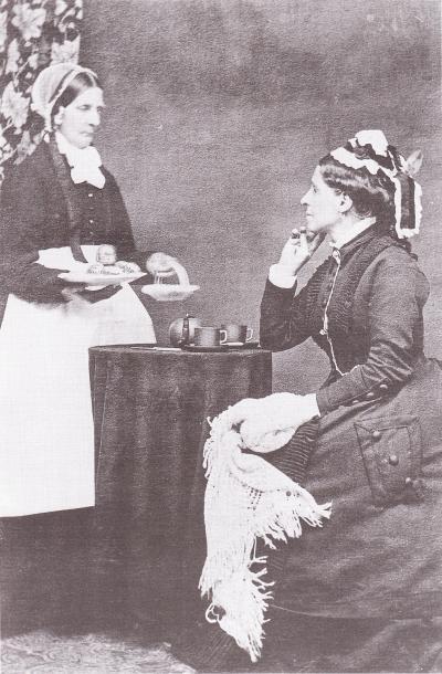 Photographie de profil d'une femme prenant le thé (à droite) et de la femme lui servant le thé (à gauche).