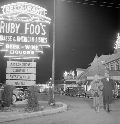 Photographie de soir de l'extérieur du restaurant. Les enseignes au néon à gauche et au fond de l'image sont illuminées. À droite, un couple sort du stationnement.