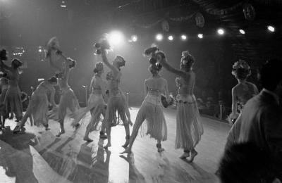 Photographie en noir et blanc d'un groupe de femmes en costume de scène qui dansent. Il y a une vue sur la salle.
