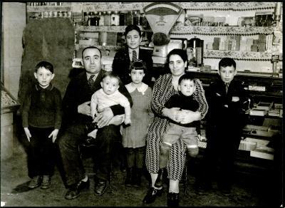 La famille DiLallo pose dans le commerce familial. Il y a le père, la mère et six enfants.