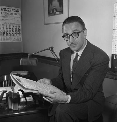 Photographie en noir et blanc d'un homme portant un complet-cravate et des lunettes à monture épaisse.