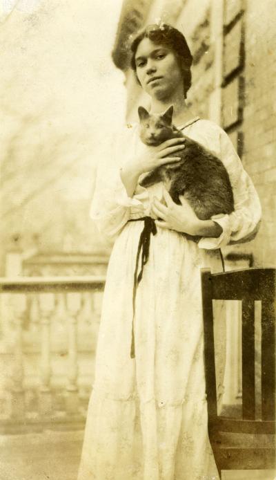 Jeune femme, en robe, tenant un chat dans ses bras, sur un balcon d'appartement.
